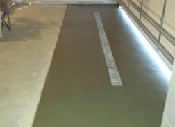 Cut out of existing garage floor to install a daylighted drain to the outside.